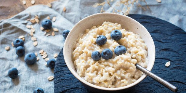 Bowl of oatmeal with blueberries on rustic dark chopping board.