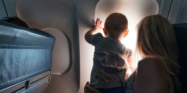 A baby looking out airplane window with her mother.