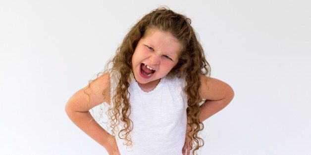A young girl (aged 8 years) with her hands on her waist and with her mouth wide open shouting with an expression of stress, anger and frustration.