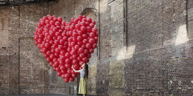Woman in empty warehouse hugging red heart made of balloons