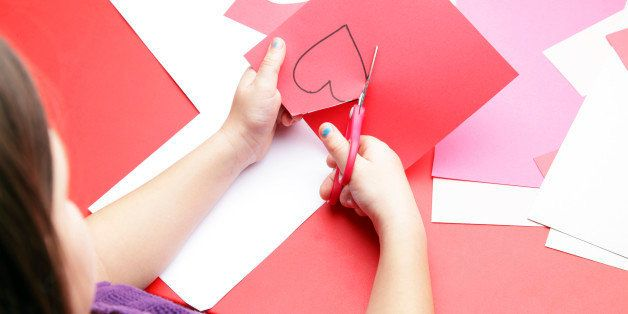 A young girl cuts out a paper heart to use for her Valentine's Day card.