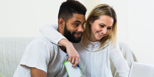 Happy smiling young spouses browsing web and making notes at home