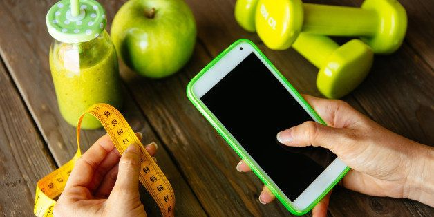 Fitness diet nutrition and workout routine smartphone app concept. Healthy green detox, apple and dumbbells for slimming down dieting. Female checking weight loss with measuring tape.