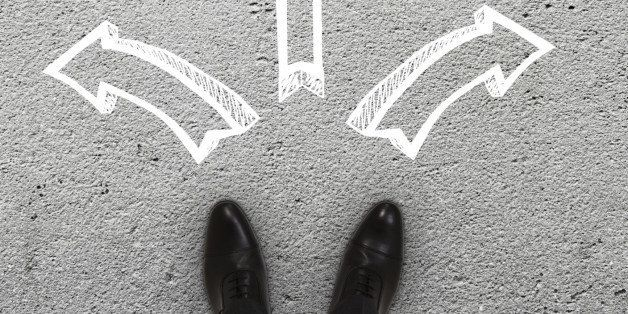pair of feet standing on a tarmac road with arrows