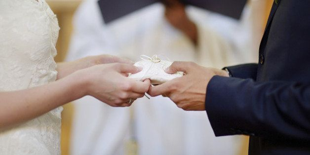 Bride and groom's hands holding wedding rings on a pillow