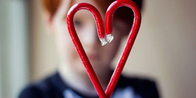 Young boy holding two red candy canes together to form a heart
