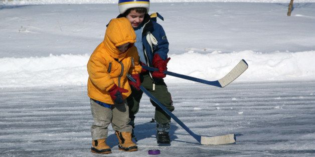 Little brothers have fun competing for a hockey puck on a outdoor pond. Each boy holds a small hockey stick and tries to hit a plastic purple puck. They wear winter jackets and boots. The picture was taken in Airdrie, Alberta, Canada. The background is snow covered.