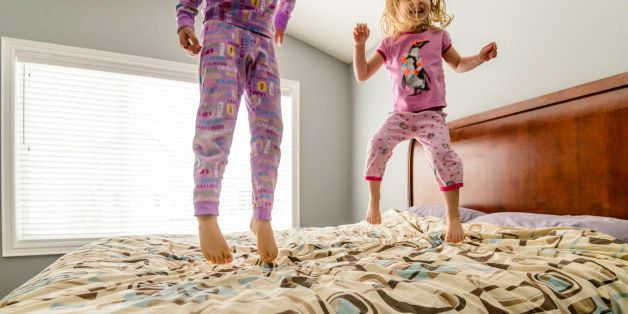 Two young girls jumping on a bed in pajamas