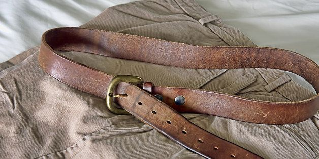 A man's belt shows the many marks of weight loss.  Six adjustments / holes equates to six inches of weight loss.  The belt sits on pants layer out on sheets of a bed, ready to be put on.