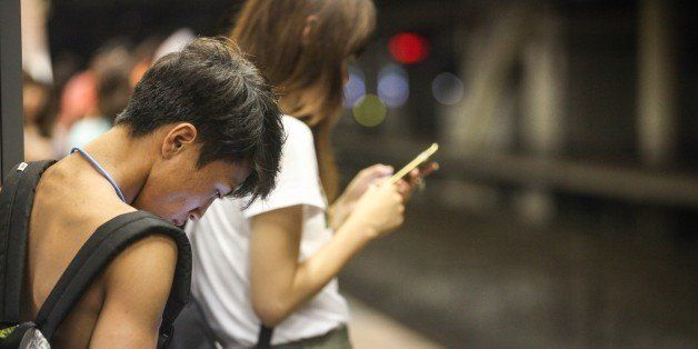 Japanese young people using smartphone on the platform of a railway station while they are waiting for the train. (rarely seen shirtless style in Jspan)