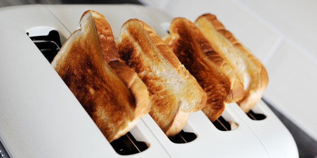Four slices of white toasted bread in a four slice toaster.