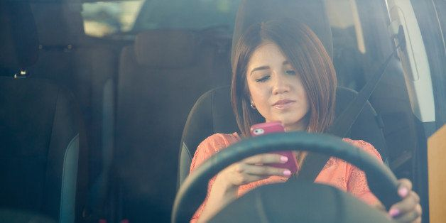 Portrait of a young woman texting on her smartphone while driving a car