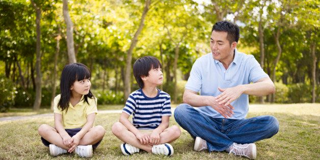asian father and two children sitting on grass having an interesting conversation, outdoors in a park.
