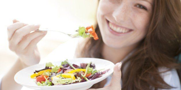 Young woman eating a salad.