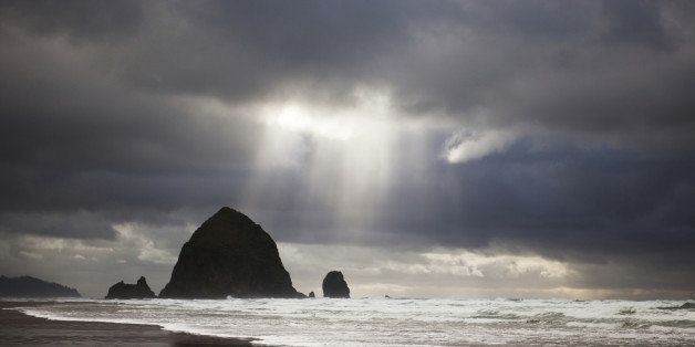 'Landscape of Cannon Beach, Oregon in the winter during a stormfront.  A sliver of light shines down over Haystack Rock.  Focus on the water.'
