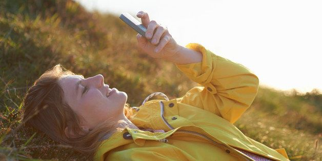 A woman lays down in the grass and uses her phone.
