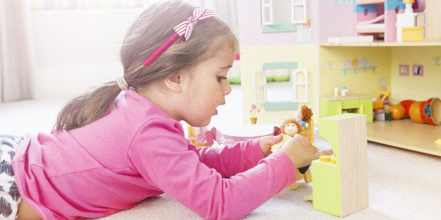 Young girl plays with dolls in dolls house.