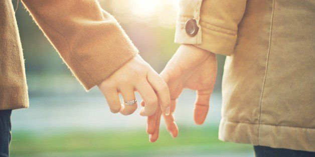 Happy couple holding hands in sunset light.