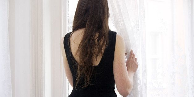 Young woman gazing out of window with a sense of melancholy, longing and contemplation. Digital and indoor photography.