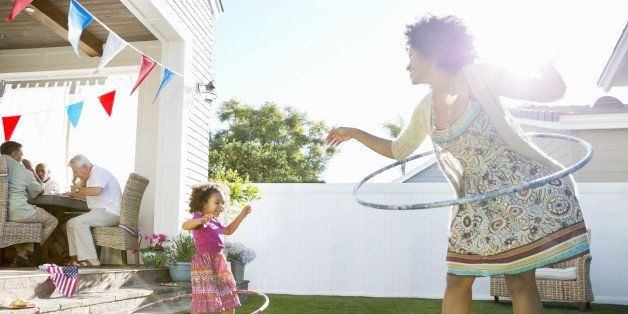 Cheerful mother and daughter twirling hula hoops on lawn