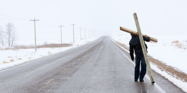 A man carrying a cross and walking down a desolate highway in winter. Easter theme. Additional themes are religion, spirituality, forgiveness, salvation, grace, mercy, love, crucifixion, burdens, suffering, journey, hope, and Good Friday. Unrecognizable Caucasian man in his 30s. This image is a remote highway in Alberta, Canada during a spring snow storm. Panorama.
