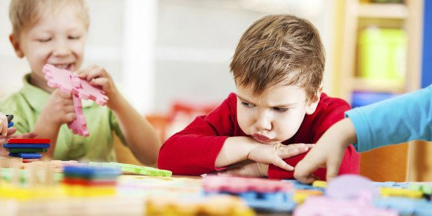 Small angry looking boy looking at the toys.