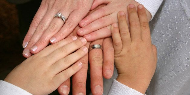 A new family at the wedding, blending Mom and her two children with Dad and his child, making a new family with stepchildren.  The husband and wife are wearing rings.