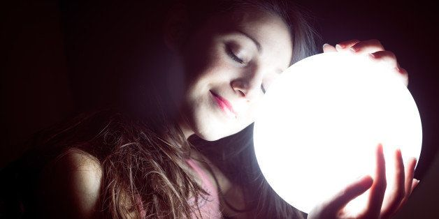 closeup image of beautiful young sleeping woman holding ball of light and smiling happily