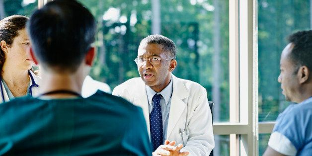 Mature male doctor leading discussion in medical team meeting in conference room in hospital