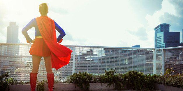 Superhero standing on city rooftop