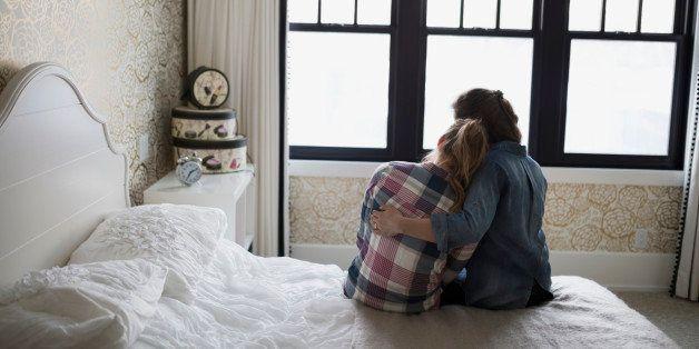 Mother hugging teenage daughter in bedroom