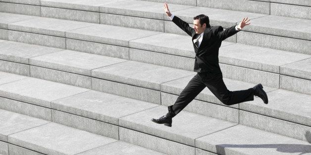 Businessman leaping on steps