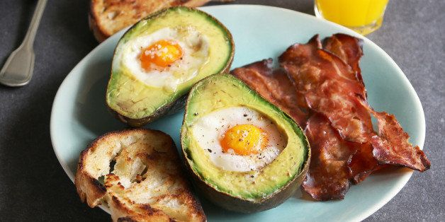Breakfast with eggs baked in avocado,bacon ,bread toast and orange juice