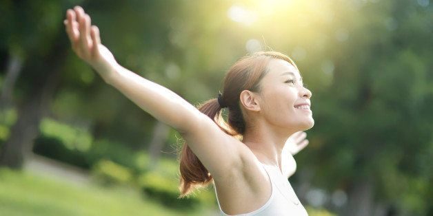 Carefree and free cheering woman in the park. girl raising her arms up smiling happy. asian beauty