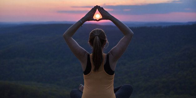 Woman meditates on a mountain top at sunset at White Rock Mountain in Arkansas.