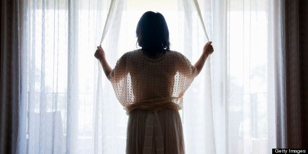 a woman opening curtains of hotel room