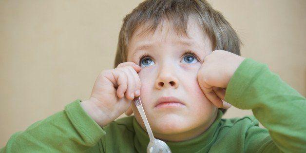 Portrait young boy gazing upwards, while eating