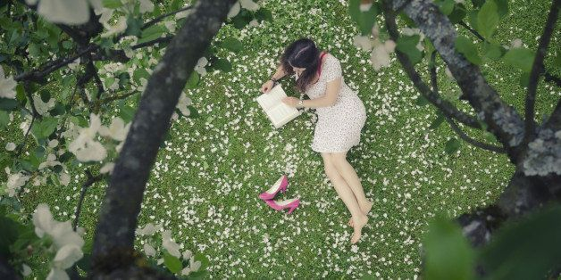 Young woman in a meadow full of apple petals - from above - reading a book - image cross processedmore photos of the same session: