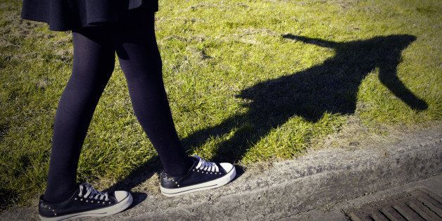 Girls legs walking along the edge of a pavement.
