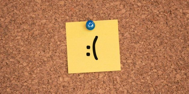 A frowning face drawn on a post-it.