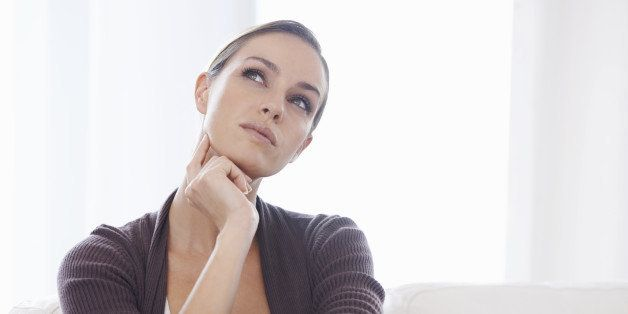 A young woman sitting on her couch looking thoughtful