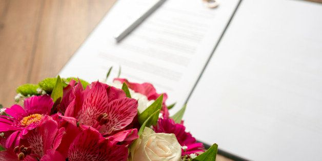 Marriage Contract with Pen and Bouquet of Fresh Beautiful Flowers on Top of a Wooden Table.