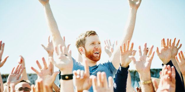 Smiling man standing with arms raised overhead in cheering crowd in stadium at sporting event