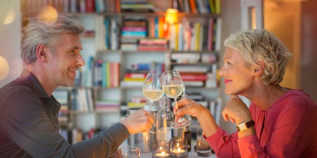 Older couple toasting each other at romantic dinner