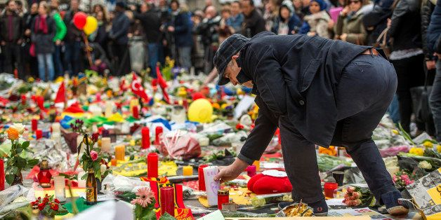 A man lays a candle as people gather to pay tribute to the victims of the Brussels attacks on the Place de la Bourse (Beursplein) in central Brussels, on March 24, 2016,  two days after a triple bomb attack, which responsibility was claimed by the Islamic State group, hit Brussels' airport and the Maelbeek - Maalbeek subway station, killing 31 people and wounding 300 others. A grieving Belgium hunted two fugitive suspects after bombings that struck at the very heart of Europe, as security authorities faced mounting criticism over the country's worst-ever attacks.  / AFP / PHILIPPE HUGUEN        (Photo credit should read PHILIPPE HUGUEN/AFP/Getty Images)