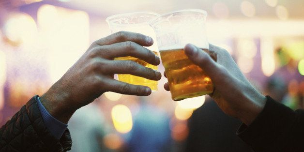 Two friends toasting to the good times with plastic cups of beer - Music Festival