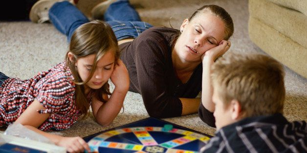 A mother nods off to sleep as her two children go on playing a board game.