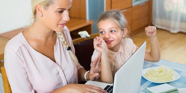 Tired businesswoman irritated as little daughter diverts her from laptop at home
