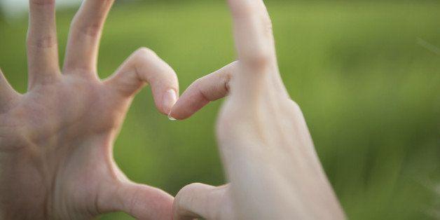 Finger frame in heart shape, selective focus