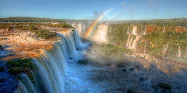 Iguazu falls and rainbow against blue sky.